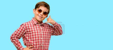 Photo pour Enfant de beau bébé aux yeux verts heureux et excité montrant appel moi le geste avec la main en forme de téléphone sur fond bleu - image libre de droit