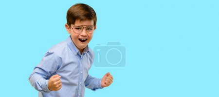 Handsome toddler child with green eyes happy and excited celebrating victory expressing big success, power, energy and positive emotions. Celebrates new job joyful over blue background