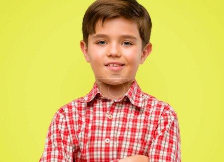 Photo pour Beau tout-petit enfant aux yeux verts avec les bras croisés confiant et heureux avec un grand sourire naturel riant sur fond jaune - image libre de droit