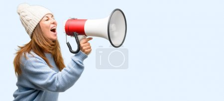 Photo for Middle age woman wearing wool winter cap communicates shouting loud holding a megaphone, expressing success and positive concept, idea for marketing or sales isolated blue background - Royalty Free Image