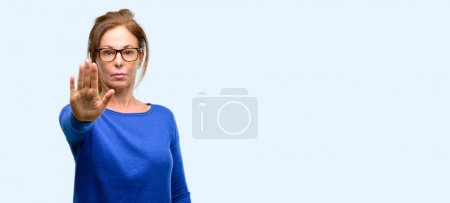 Middle age woman wearing wool sweater and glasses annoyed with bad attitude making stop sign with hand, saying no, expressing security, defense or restriction, maybe pushing isolated blue background