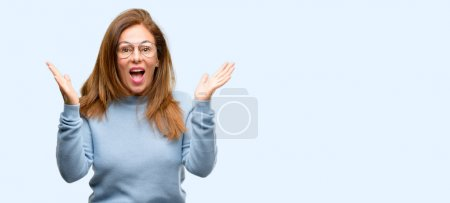 Photo for Middle age woman wearing wool sweater and cool glasses happy and surprised cheering expressing wow gesture isolated blue background - Royalty Free Image