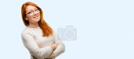 Photo for Beautiful young redhead woman with crossed arms confident and happy with a big natural smile laughing isolated over blue background - Royalty Free Image