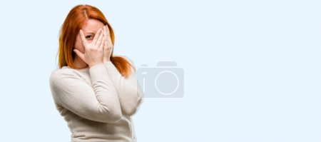 Beautiful young redhead woman smiling having shy look peeking through fingers, covering face with hands looking confusedly broadly isolated over blue background