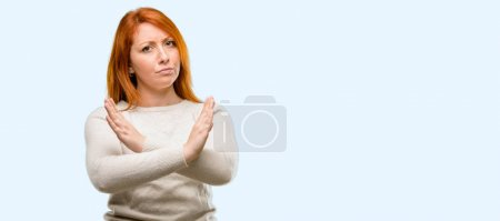 Beautiful young redhead woman annoyed with bad attitude making stop sign crossing hands, saying no, expressing security, defense or restriction isolated over blue background