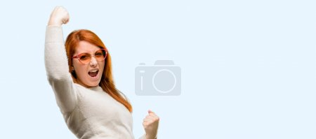 Photo for Beautiful young redhead woman happy and excited celebrating victory expressing big success, power, energy and positive emotions. Celebrates new job joyful isolated over blue background - Royalty Free Image