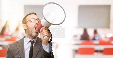 Teacher man using glasses communicates shouting loud holding a megaphone, expressing success and positive concept, idea for marketing or sales at classroom