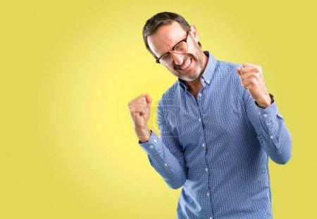Photo pour Beau homme d'âge moyen heureux et excité célébrant la victoire exprimant le grand succès, la puissance, l'énergie et les émotions positives. Célébre nouveau travail joyeux - image libre de droit