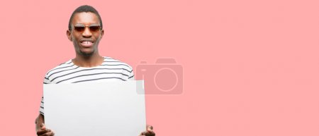 African black man wearing sunglasses holding blank advertising banner, good poster for ad, offer or announcement, big paper billboard