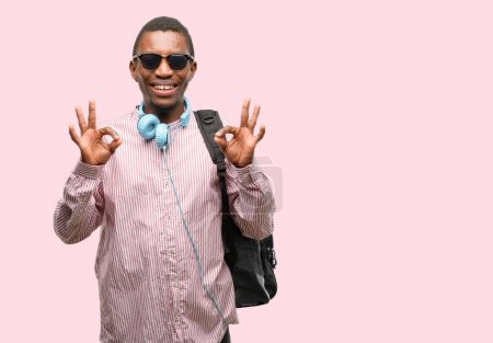 Photo for African black man student doing ok sign gesture with both hands expressing meditation and relaxation - Royalty Free Image