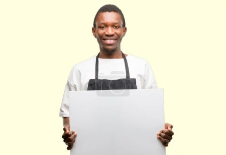African man shop owner wearing apron holding blank advertising banner, good poster for ad, offer or announcement, big paper billboard