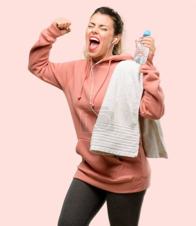 Young sport woman wearing workout sweatshirt happy and excited celebrating victory expressing big success, power, energy and positive emotions. Celebrates new job joyful