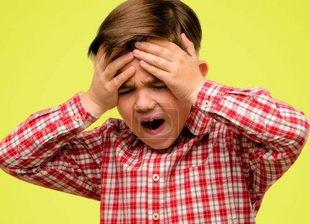 Enfant de la Bel Bambin avec maintien de stress yeux verts mains sur la tête, terrifié dans la panique, criant sur fond jaune
