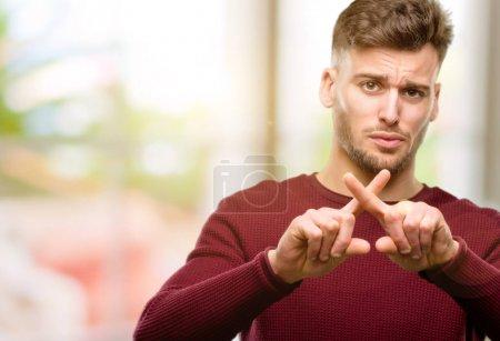 Photo pour Beau jeune homme agacé avec une mauvaise attitude faisant signe d'arrêt avec la main, disant non, exprimant la sécurité, la défense ou la restriction, peut-être pousser - image libre de droit