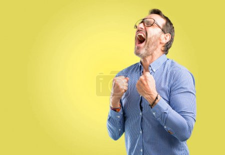 Photo for Handsome middle age man happy and excited celebrating victory expressing big success, power, energy and positive emotions. Celebrates new job joyful - Royalty Free Image