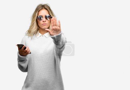 Photo pour Jeune belle femme utilisant un smartphone agacé avec une mauvaise attitude faisant signe d'arrêt avec la main, disant non, exprimant la sécurité, la défense ou la restriction, peut-être pousser - image libre de droit