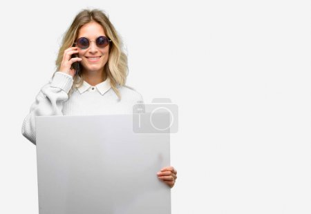 Young beautiful woman using smartphone holding blank advertising banner, good poster for ad, offer or announcement, big paper billboard