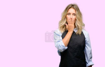 Foto de Joven tienda propietario usar delantal negro cubre boca en estado de shock, miradas tímidas, expresando conceptos de silencio y error, miedos - Imagen libre de derechos