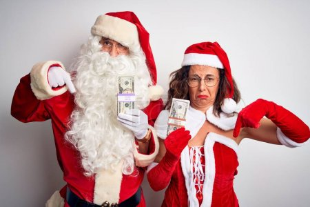 Photo for Senior couple wearing Santa Claus costume holding dollars over isolated white background Pointing down looking sad and upset, indicating direction with fingers, unhappy and depressed. - Royalty Free Image