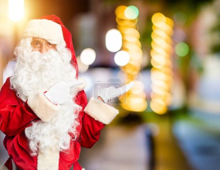 Photo for Middle age handsome man wearing Santa Claus costume and beard standing amazed and smiling to the camera while presenting with hand and pointing with finger. - Royalty Free Image