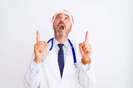 Photo for Middle age doctor man wearing christmas hat and stethoscope over isolated white background amazed and surprised looking up and pointing with fingers and raised arms. - Royalty Free Image