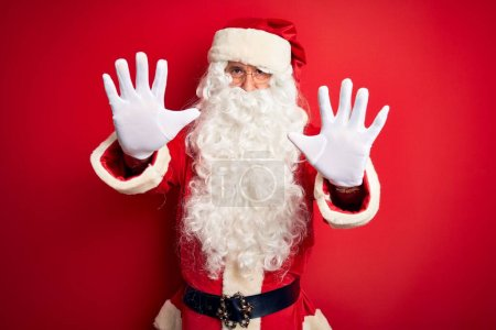 Photo for Middle age handsome man wearing Santa costume standing over isolated red background doing stop gesture with hands palms, angry and frustration expression - Royalty Free Image