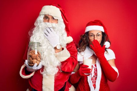 Photo for Couple wearing Santa costume holding jar of cookies and milk over isolated red background cover mouth with hand shocked with shame for mistake, expression of fear, scared in silence, secret concept - Royalty Free Image
