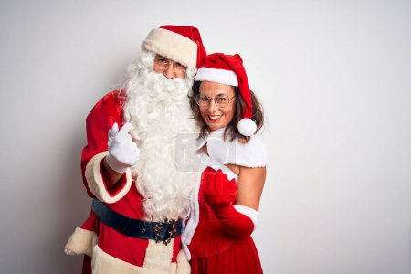 Photo for Middle age couple wearing Santa costume hugging over isolated white background Beckoning come here gesture with hand inviting welcoming happy and smiling - Royalty Free Image