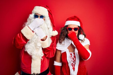 Photo for Middle age couple wearing Santa costume and sunglasses over isolated red background smelling something stinky and disgusting, intolerable smell, holding breath with fingers on nose. Bad smells concept. - Royalty Free Image