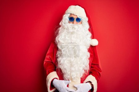 Photo for Middle age man wearing Santa Claus costume and sunglasses over isolated red background with a happy and cool smile on face. Lucky person. - Royalty Free Image