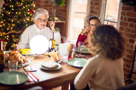 Photo for Beautiful group of women smiling happy and confident. Eating roasted turkey celebrating christmas at home - Royalty Free Image