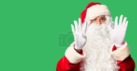 Photo for Middle age handsome man wearing Santa Claus costume and beard standing showing and pointing up with fingers number nine while smiling confident and happy. - Royalty Free Image
