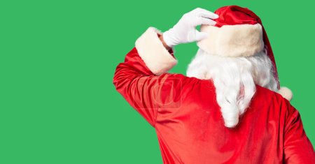 Photo for Middle age handsome man wearing Santa Claus costume and beard standing Backwards thinking about doubt with hand on head - Royalty Free Image