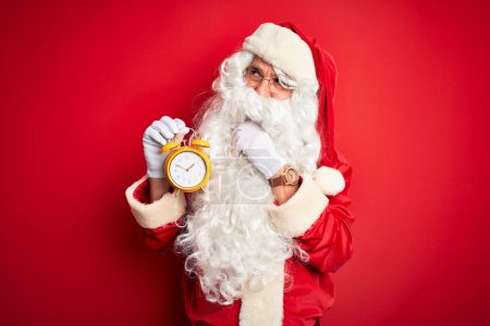 Photo for Senior man wearing Santa Claus costume holding alarm clock over isolated red background serious face thinking about question, very confused idea - Royalty Free Image