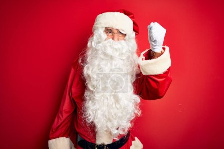 Photo for Middle age handsome man wearing Santa costume standing over isolated red background angry and mad raising fist frustrated and furious while shouting with anger. Rage and aggressive concept. - Royalty Free Image