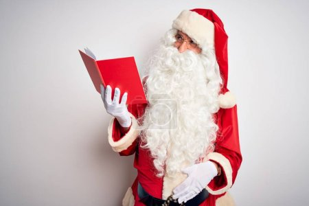 Photo for Middle age man wearing Santa Claus costume reading book over isolated white background smiling looking to the side and staring away thinking. - Royalty Free Image