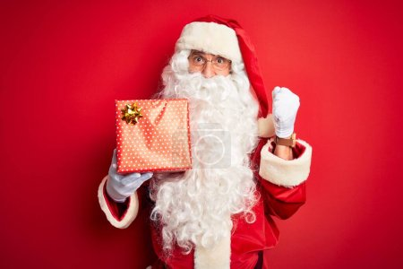 Photo for Middle age man wearing Santa Claus costume holding gift over isolated red background screaming proud and celebrating victory and success very excited, cheering emotion - Royalty Free Image