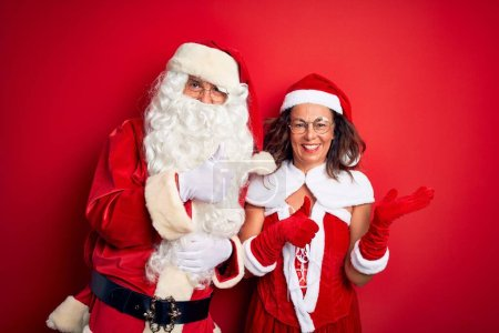 Photo for Middle age couple wearing Santa costume and glasses over isolated red background Showing palm hand and doing ok gesture with thumbs up, smiling happy and cheerful - Royalty Free Image