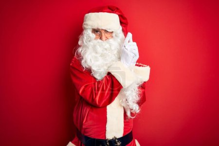 Photo for Middle age handsome man wearing Santa costume standing over isolated red background Holding symbolic gun with hand gesture, playing killing shooting weapons, angry face - Royalty Free Image