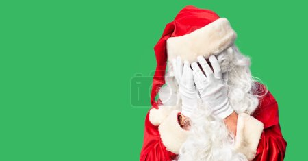 Photo for Middle age handsome man wearing Santa Claus costume and beard standing with sad expression covering face with hands while crying. Depression concept. - Royalty Free Image