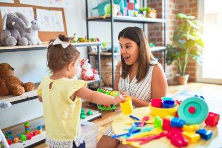 Photo pour Jeune enseignant et tout-petit jouant avec de la vaisselle, de la coutellerie et des tasses jouet sur la table à la maternelle - image libre de droit
