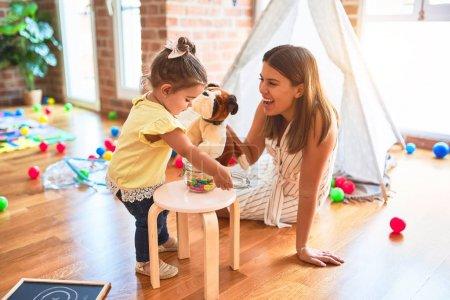 Photo pour Jeune beau professeur jouant avec une poupée de chien et un tout-petit tenant un pot de boules de chocolat au jardin d'enfants - image libre de droit