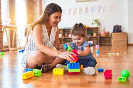 Photo pour Jeune enseignant et tout-petit jouant avec des pièces de construction jouet à la maternelle - image libre de droit