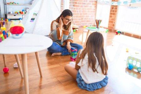 Photo pour Magnifique enseignant et tout-petit jouant avec des blocs de bois autour de nombreux jouets à la maternelle. - image libre de droit