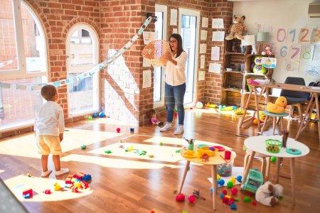 Photo pour Magnifique professeur et tout-petit jouant au basket-ball en jouant à la balle et au panier d'osier autour de nombreux jouets à la maternelle. - image libre de droit