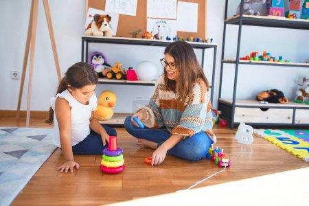 Photo pour Magnifique enseignant et tout-petit construisant une pyramide à l'aide de cerceaux autour de beaucoup de jouets à la maternelle. - image libre de droit