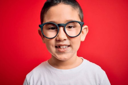 Photo for Young little smart boy kid wearing nerd glasses over red isolated background with a happy face standing and smiling with a confident smile showing teeth - Royalty Free Image