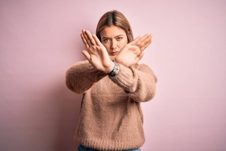 Photo pour Young beautiful blonde salope woman wearing winter wool sweater over pink isolated background Rejection expression crossing arms and palms doing negative sign, angry face - image libre de droit
