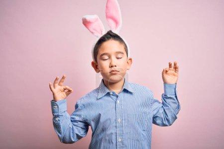 Photo pour Jeune garçon portant des oreilles de lapin de Pâques sur un fond rose isolé se détendre et sourire les yeux fermés faire un geste de méditation avec les doigts. Concept du yoga. - image libre de droit