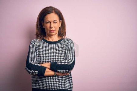 Photo pour Magnifique femme d'âge moyen portant un chandail décontracté, se tenant debout sur un fond rose isolé, sceptique et nerveux, expression désapprobatrice sur le visage avec les bras croisés. Personne négative. - image libre de droit